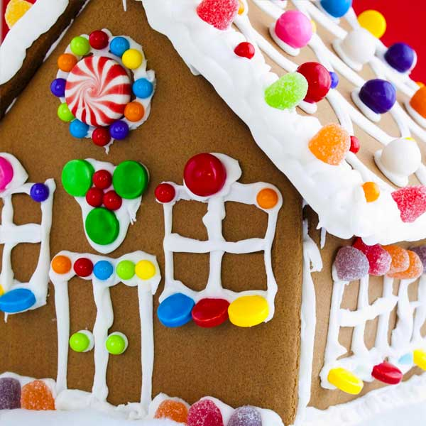 Decorated gingerbread house on red background