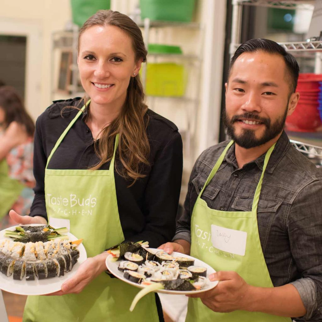 Couples cooking class making beautiful sushi rolls at Taste Buds Kitchen