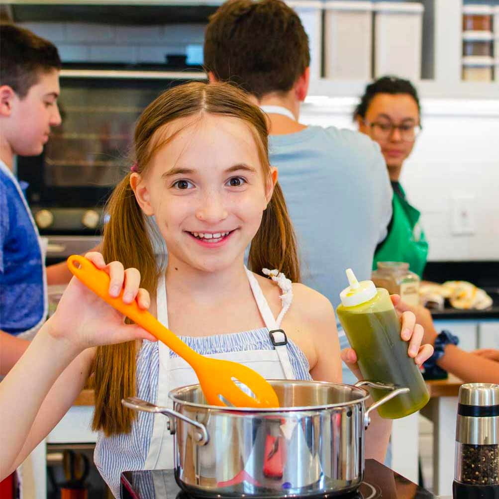 Girl sautéing with olive oil at a Taste Buds Kitchen Cooking Camp